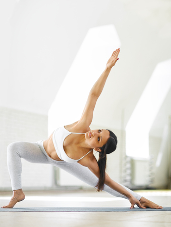 Portrait of athletic young woman wearing white sportswear working out in yoga studio with white wall background. Sporty model practicing yoga and stretching body on the blue mat. Healthy lifestyle, morning exercises, meditation.
