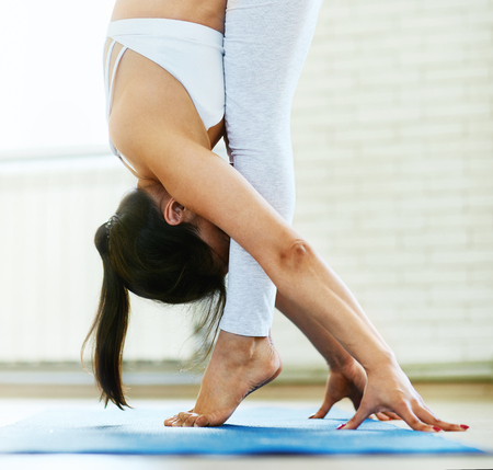 Young sporty woman in white sportswear practicing flexibility yoga exercise in a gym with sunlight background. Yoga model standing in forward bend exercise, head to knees uttanasana pose on mat close up. Healthy lifestyle, morning exercises, meditation. Side view