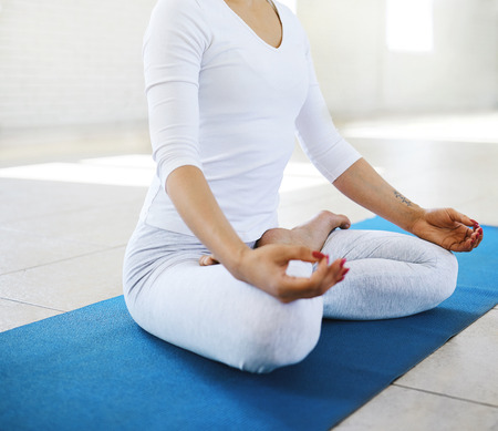 Young sporty woman in white sportswear practicing flexibility yoga exercise in a gym with sunlight background. Yoga model sitting sitting in Padmasana lotus pose. Feeling so comfortable and relax. Slim model practice morning meditation.