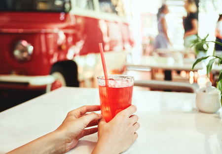 Woman drinking red lemonade or cocktail in cafe. Hands holding a cocktail on the foreground. Young female enjoying a glass of soft drink with a straw sitting at a restaurant table. Summertime concept. Side view. Banque d'images