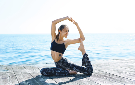 Photo of young athletic woman make yoga exercises on seaside. Side view of athletic lady doing Pigeon Pose with Raised Arms against blue sea on wooden pier. Eka Pada Rajakapotasana Yoga Pose. Healthy lifestyle, morning exercises, meditation.