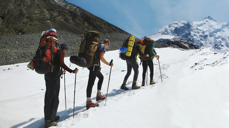 A group of mountaineers climbs to the top of a snow-capped mountain. Climbers are hiking on mountain peaks ridge. , Beautiful mountaineering tourism trekking. Concept of Motivation, Teamwork, Leadership. Imagens - 121774731