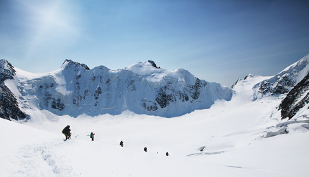 A group of mountaineers climbs to the top of a snow-capped mountain. Climbers are hiking on mountain peaks ridge. , Beautiful mountaineering tourism trekking. Concept of Motivation, Teamwork, Leadership. Imagens - 121774730