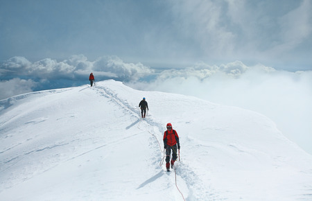 A group of mountaineers climbs to the top of a snow-capped mountain. Climbers are hiking on mountain peaks ridge. , Beautiful mountaineering tourism trekking. Concept of Motivation, Teamwork, Leadership.