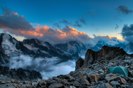 Fantastic morning landscape of rocky mountains at sunrise. Dramatic clouds in burning sky, morning light.