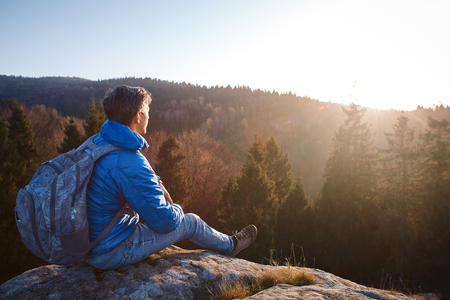 Man sitting on edge of cliff against background of sunrise. Adult tourist with backpack looking to misty hilly valley below.