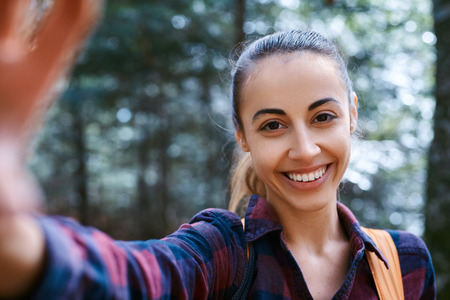 Portrait of beautiful happy stylish traveling woman taking a selfie on the camera phone with forest background. Young female hiker walking on the trail in the woods.