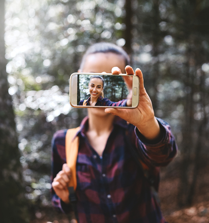 Beautiful happy stylish traveling woman taking a selfie on the camera phone with forest background. Portrait of young female hiker walking on the trail in the woods. Imagens - 122775934