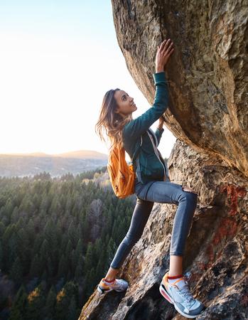 giovane donna attraente escursionista arrampicata sulla roccia al tramonto. Donna che fa un'escursione su una scogliera con lo zaino. Concetto di stile di vita sportivo di viaggio. Archivio Fotografico