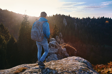 Man is standing on edge of cliff against background of sunrise. Adult tourist with backpack looking to misty hilly valley below.