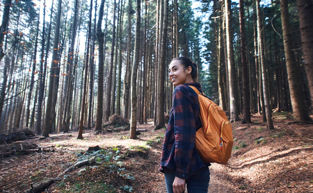 Portrait of a woman hiker walking on the trail in the woods. Beautiful happy stylish traveling girl with backpack on a forest background. Imagens