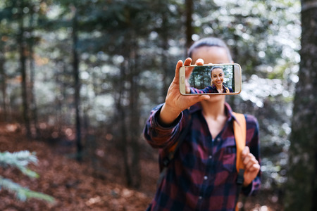 Beautiful happy stylish traveling woman taking a selfie on the camera phone with forest background. Portrait of young female hiker walking on the trail in the woods. Imagens - 122767416