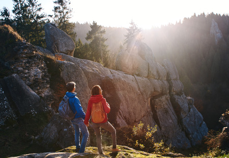 Two travelers standing on the cliff against wooded hills and cloudy sky at sunrise. Couple standing, holding hands, greeting the sun. Tourists with backpack looking to misty hilly valley below.