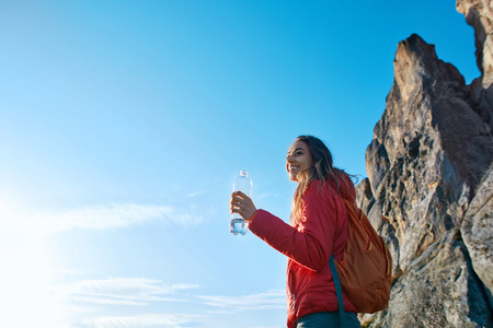 woman hiker with backpack, wearing in red jacket, standing on edge of cliff against a blue sky background. Young female holds a bottle of water in hand and enjoying.