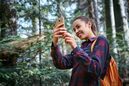 Beautiful happy stylish traveling woman taking photo on the camera phone with forest background. Portrait of young female hiker walking on the trail in the woods.