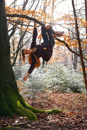 Young happy woman hanging on tree and laughs in woods with orange backpack. Funny girl fooling around on a forest background. Travel, emotions, happy positive concept. Imagens - 122767420