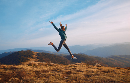 Happy woman hiker jumping on mountain ridge on blue cloudy sky and mountains background. Travel and active lifestyle concept. Imagens