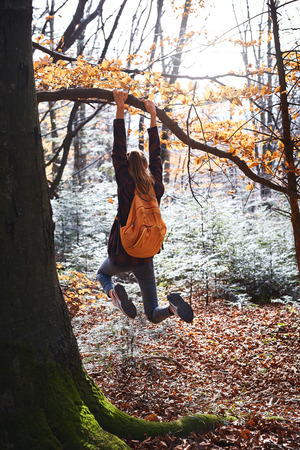 Young happy woman hanging on tree in woods with orange backpack. Funny girl fooling around on a forest background. Back view. Travel, emotions, happy positive concept. Imagens - 122767425