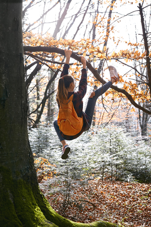 Young happy woman hanging on tree in woods with orange backpack. Funny girl fooling around on a forest background. Back view. Travel, emotions, happy positive concept.