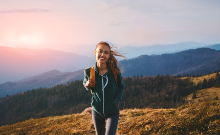 Portrait of a happy woman hiker standing on the slope of mountain ridge against mountains, sunset sky background. The woman is happy and looking at camera. Travel and active lifestyle concept.