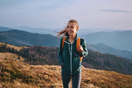 Portrait of a happy woman hiker standing on the slope of mountain ridge against mountains, blue cloudy sky on background. The woman is happy and looking at camera. Travel and active lifestyle concept.