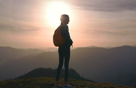 Silhouette of young woman standing on edge of mountain and enjoying life on sunset sky and mountains background. Travel and active lifestyle concept.