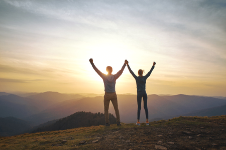 Silhouette of man and woman standing on edge of mountain and holding hands up on sunset sky and mountains background. Travel and active lifestyle concept.