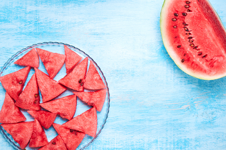Watermelon slices without skin on the transparent glass plate on blue wooden table. Top view, flat lay. Summertime concept