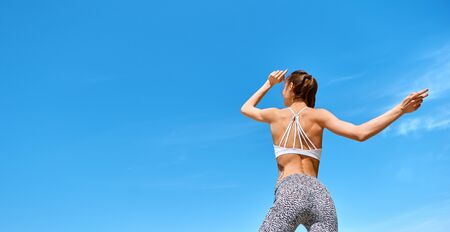 attractive sports with tanned fit body woman posing against blue sky. Fitness woman in sport wear with muscular back and tight in leggings. back wiew.