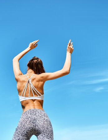attractive sports woman with tanned fit body posing with raised arms against blue sky at hot sunny summer day. Fitness woman in sport wear with muscular back and tight in leggings. back wiew.