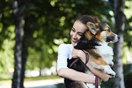 Welsh Corgi Pembroke dog and smiling happy woman together in a park outdoors. Young female in white shirt embracing, holding a her cute pet. Concept friendship with dog and human, cute moments, happines.