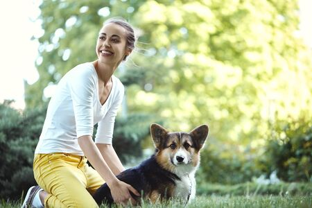 Welsh Corgi Pembroke dog and smiling happy woman together in a park outdoors. Young female sitting on the grass with her pet. Concept friendship with dog and human, cute moments, happines. Focus on the dog. Imagens