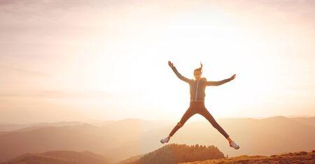 silhouet van jonge vrouw die van het leven geniet en op berg springt tegen oranje zonsonderganghemel en bergenachtergrond