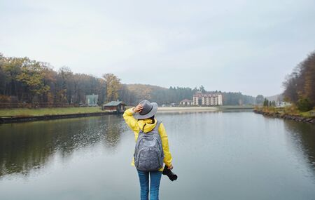 Stylish young woman in yellow waterproof raincoat and hat, standing on pier by the lake in the park at autumn. Female holding a camera, enjoying view over the lake at cloudy autumn day. Back view. Stockfoto