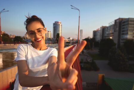 Bright summer lifestyle portrait of young pretty woman in eyewear, red skirt and white T-shirt, showing peace sign with hand or V sign with fingers, standing on the bright red bridge at evening with city background. Trendy hipster girl smiling, looking into camera, enjoying warm summer day on sunset. Bright color, summertime and lifestyle concept.