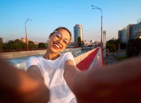 Bright summer lifestyle portrait of young pretty woman in eyewear, red skirt and white T-shirt, taking a selfie on camera, standing on the bright red bridge at evening with city background. Trendy hipster girl smiling, looking into camera, enjoying warm summer day on sunset. Bright color, summertime and lifestyle concept.