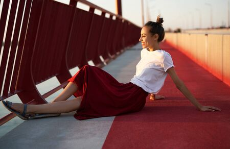 Bright summer lifestyle portrait of young pretty woman in red skirt and white T-shirt, sitting on a bright red floor on the bridge. Trendy stylish girl relaxing, enjoying warm summer day on sunset.