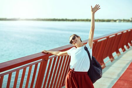 Bright summer lifestyle portrait of young pretty woman in sunglasses and red skirt and white T-shirt, walking on the bright red bridge, the river on background. Trendy hipster girl smiling, having fun, enjoying warm summer day. Bright color, summertime and lifestyle concept.