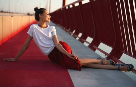 Bright summer lifestyle portrait of young pretty woman in red skirt and white T-shirt, posing, sitting on a bright red floor on the bridge. Trendy stylish girl relaxing, enjoying warm summer day on sunset.