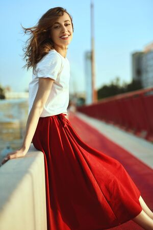 Bright lifestyle portrait of smiling pretty woman in red skirt and white T-shirt, posing, sitting on parapet at the bridge, blowing hair by wind. Trendy stylish girl relaxing, enjoying the sunset view and light fresh wind. Imagens