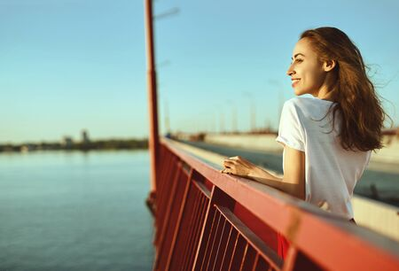 Bright lifestyle portrait of young pretty woman in red skirt and white T-shirt, posing, standing on a bright red floor on the bridge. Trendy stylish girl relaxing, enjoying the sunset and river view and light fresh wind.