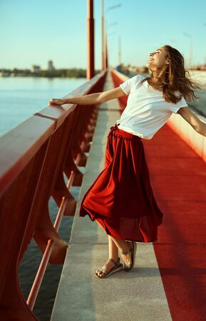 Bright lifestyle portrait of young pretty woman in red skirt and white T-shirt, posing, standing on a bright red floor on the bridge, blowing hair by wind. Trendy stylish girl relaxing, enjoying the sunset view and light fresh wind.