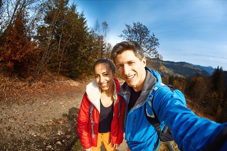 smiling happy couple hikers with backpacks making selfie on the woods and blue sky background while hiking in mountains in Western Ukraine. Imagens
