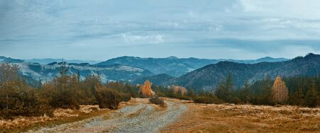 beautiful view of an autumn mountain landscape with a roug mountain road.
