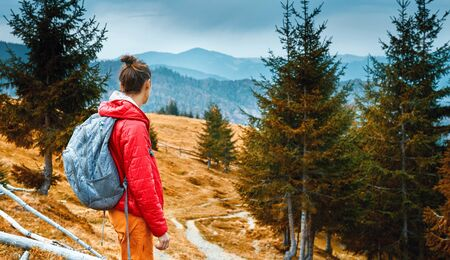back view of a woman hiker with backpack walking outdoors in the mountains. woman is standing on the mountain trail and looking forward