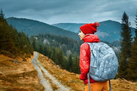 back view of a woman hiker with backpack, wearing in red jacket and orange pants, standing on the mountains background, Western Ukraine.