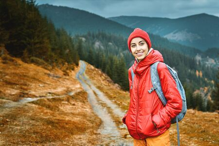woman hiker with backpack, wearing in red jacket and orange pants, standing on the mountains and woods background, Western Ukraine.