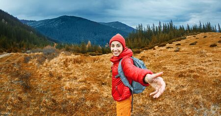 image of a young smiling woman hiker with small backpack standing on a mountain slope. Follow me, hiking, active and travel lifestyle concept.