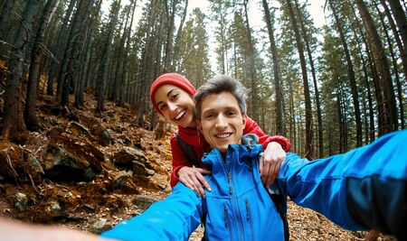 smiling happy couple hikers with backpacks making selfie on the dark dramatic mossy woods background while hiking in mountains in Western Ukraine. Imagens