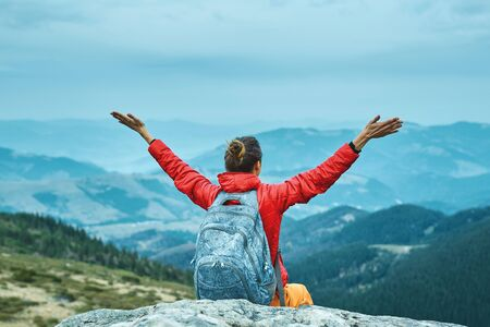 woman hiker in red jacket sitting on the cliff in mountains and sightseeing Imagens